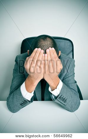 a businessman sitting in a desk with his hands in his head