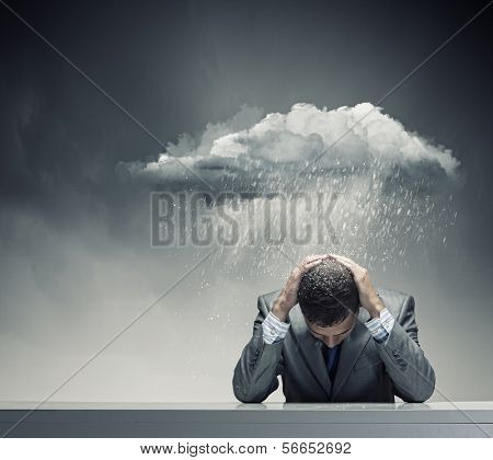 Depressed young businessman sitting wet under rain
