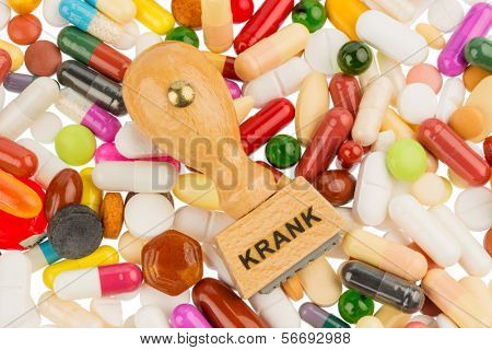 stamp on colorful tablets, symbol photo for illness, sick leave and drugs