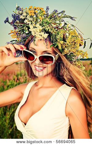 Portrait of a romantic smiling young woman in a circlet of flowers outdoors.