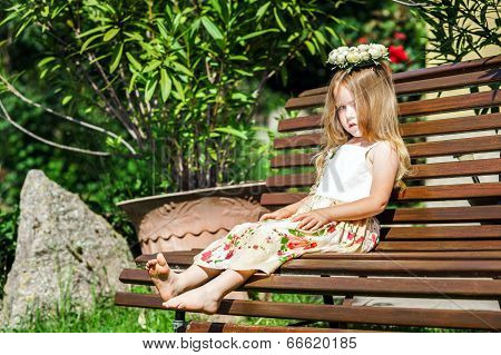 Cute Litle Barefoot Girl Sitting On The Bench