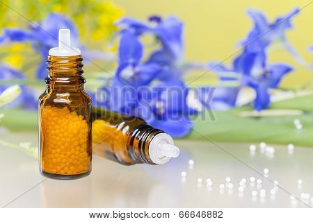 Two Bottles With Homeopathy Globules And Flowers, With White Reflecting Underground