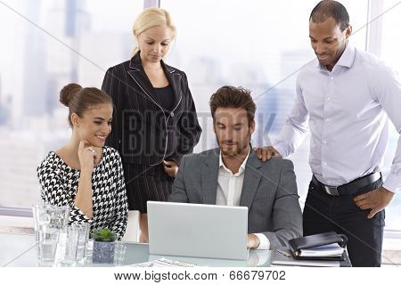 Young businesspeople in meetingroom, looking at laptop computer.