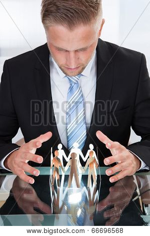 Businessman Taking Care Of Paper People