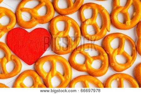 Valentine's Day Background Pretzels Pattern And Red Heart.