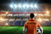 Netherlands football player holding ball against stadium full of netherlands football fans poster