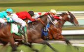 Abstract blur of racing horses and jockeys poster