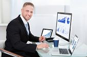 Businessman with good performance graph sitting at his desk with statistical reports spread over three monitors cheering and clasping his fists poster