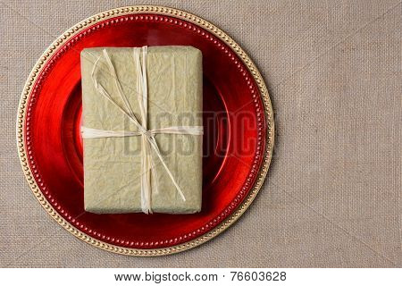 A gold tissue paper wrapped Christmas present on a red charger. The present is tied with raffia and both items are on a burlap surface. High angle shot in horizontal format with copyspace.
