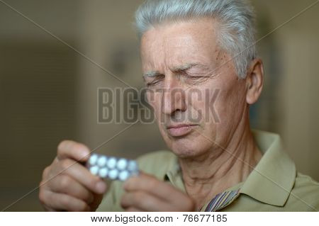Elderly ill man with pills in hand poster