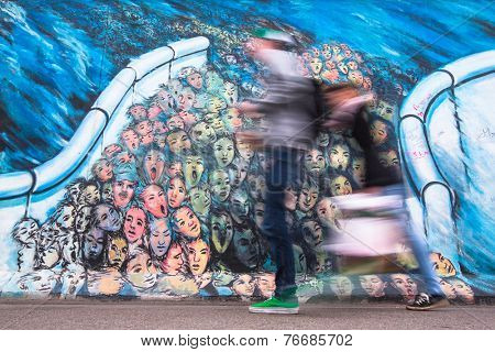 BERLIN, GERMANY - NOV 15, 2014: Fragment of graffiti on Berlin Wall at East Side Gallery - it's a 1.3 km long part of original Wall which collapsed in 1989 and now is largest world graffiti gallery.