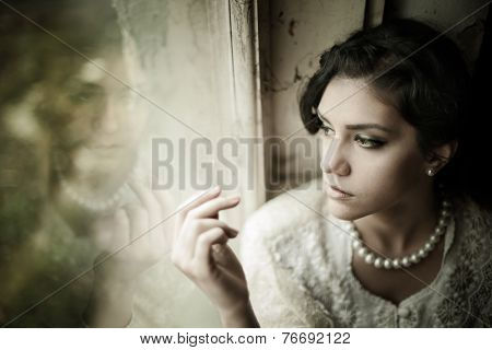 Gorgeous brunette woman with brown eyes wearing pearls looking through the window portrait poster