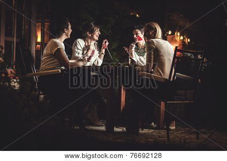 Four attractive women night out having dinner in a restaurant