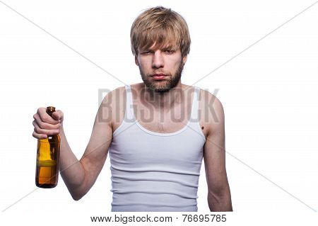 Young man with hangover holding beer bottle. After party