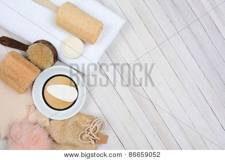 Bath and Spa still life. High angle shot of bathroom accessories including, towel, soap, loofah and sandals, on a rustic white wood surface. Items are set to the left side leaving room for your copy.