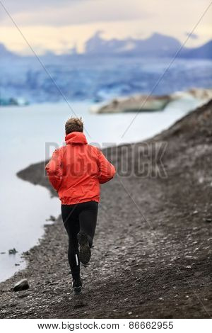 Runner man trail running training for run in beautiful nature landscape. Fit male athlete jogging and cross country running by icebergs in Jokulsarlon glacial lake in Iceland. poster