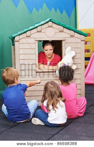 Nursery teacher using playhouse for theater play with stuffed animals for children