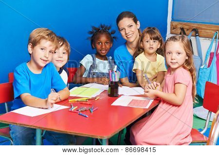 Group of children painting on table with nursery teacher in a kindergarten