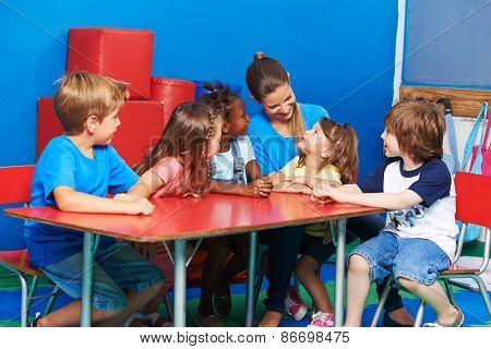 Children in circletime listining to girl talking in kindergarten