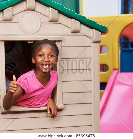 Happy african girl in playhouse holding hter thumbs up in preschool
