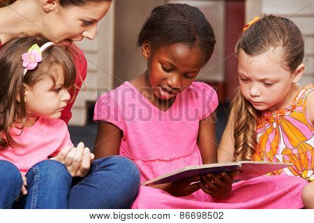 Children learning to read with nursery teacher in preschool