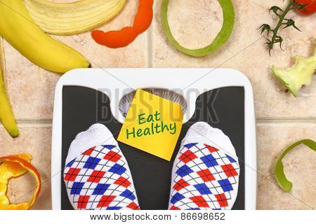 Feet on bathroom scale with Eat Healthy text fruit peals around