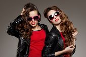Sisters twins in hipster sun glasses laughing Two fashion models Women smiling positive Friends group having fun, talking Youthful friendship youth adults people culture concept Young girls rock party poster