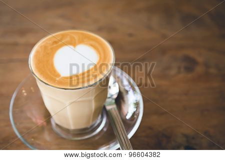 Cup of coffee with heart pattern  on wood table ( Filtered image processed vintage effect. )