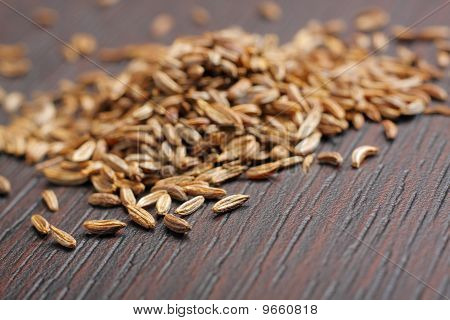 Caraway seeds (Carum carvi) on dark table. Close-up photo. poster