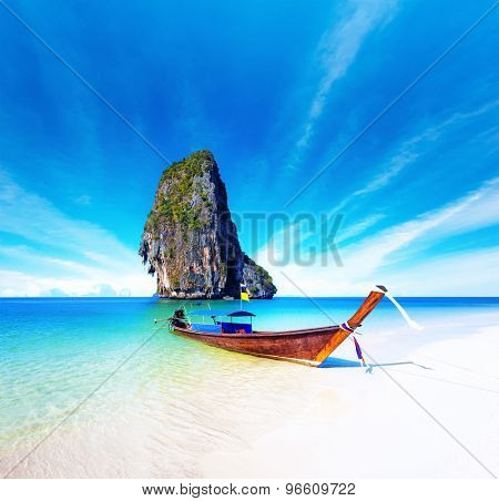 Scenic getaway background of thai boat on exotic beach of tropical island in Thailand. Clear water and blue sky at sunny summer day