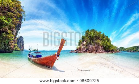 Amazing nature and exotic travel destination in Thailand. Thai tourist boat on white sand beach of small tropical island