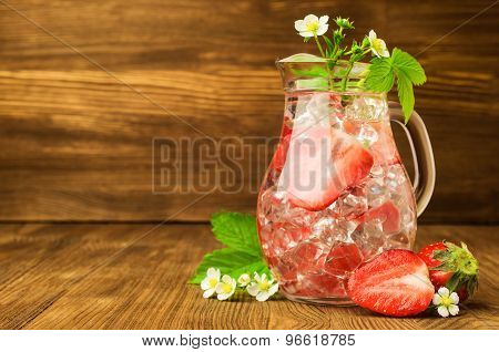 refreshing drink with a strawberry and ice in a glass jug on a wooden background poster