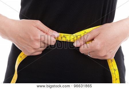 The woman in black measures her waist circumference with measuring tape on white background. poster