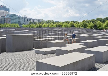 BERLIN, GERMANY - JULY 08: Young couple seated on stone block at the Memorial to the Murdered Jews of Europe. July 08, 2015 in Berlin.