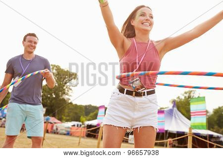 Man and woman dancing with hula hoops at a music festival