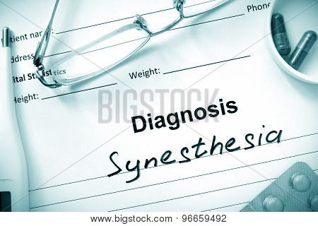 Diagnosis Synesthesia and tablets on a wooden table.