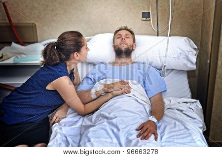 Young Couple At Hospital Room Man Lying In Bed Worried Woman Holding His Hand Caring