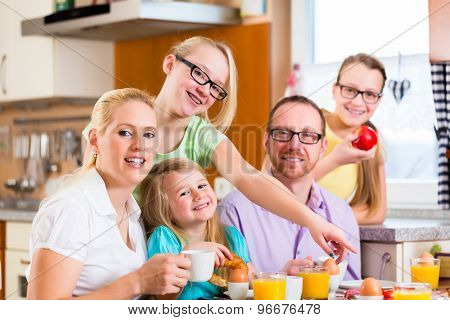 Family having joint breakfast in kitchen eating and drinking