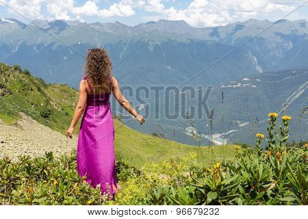 woman in evening dress standing back in the mountains