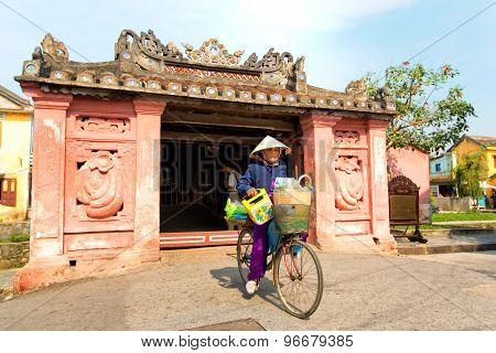 Hoian, Vietnam-jan 23:j Woman Riding A Bicycle Near Japanese Pagoda (or Bridge Pagoda) In Hoi An Anc
