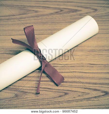 diploma on wood table background vintage style