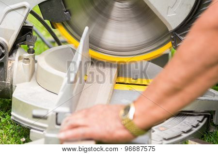 young man working with an electrical sander holding wood plank poster