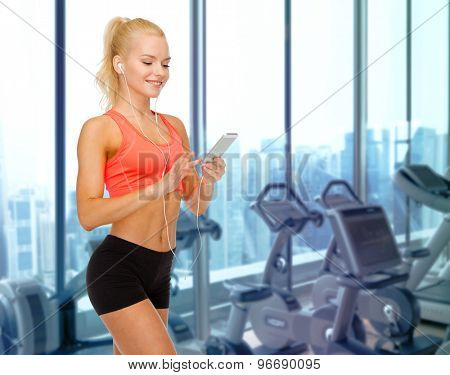 sport, fitness, technology and people concept - smiling sporty woman with smartphone and earphones listening to music over gym machines background