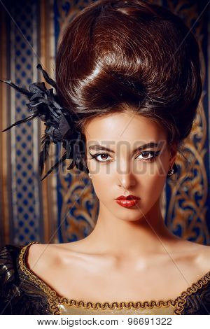 Close-up portrait of a beautiful baroque woman in elegant historical dress and with barocco updo hairstyle over vintage background. Renaissance. Barocco. Fashion.