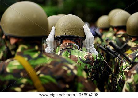 Soldier In Camouflage Uniform Arranging His Helmet