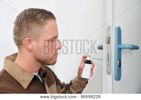 Close-up Of Young Male Carpenter Lubricating Door With Oil poster