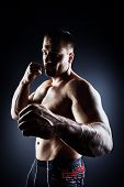 Strong muscular man fighting with fists. Martial arts. Fist fights, boxing. Bodybuilding. Black background. poster