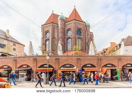 MUNICH BAVARIA GERMANY - APRIL 06 2016: Pedestrians browse shops and stalls beneath St. Peter's Church Peterskirche along Viktualienmarkt market street in Munich Bavaria Germany.