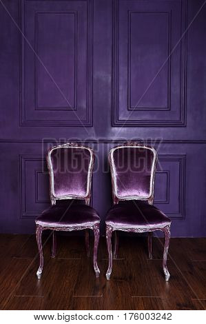 Two elegant chairs on the background wall