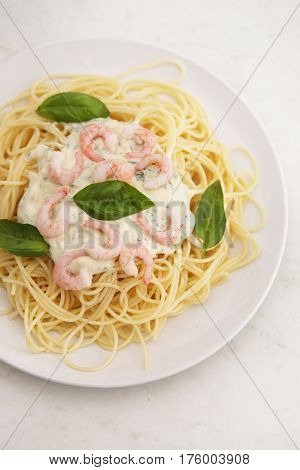 spaghetti with white sauce and shrimps on a white plate